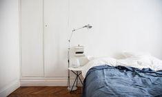 Chambre épurée dans un appartement parisien, linge de lit bleu vintage, et lampadaire Jieldé, Sur The Socialite Family, Paris.