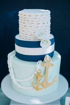 Beautiful blue nautical birthday cake decorated with roses, rope, and anchor