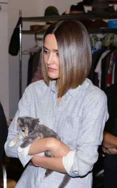Rose Byrne with very shiny hair, a simple top, and an adorable kitten