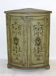 Pair of Italian, Neoclassical, painted corner cabinets: With bow front tops above panel inset doors, raised on bracket feet, the whole painted with scrolls and flowering leafage on a pale green ground.  Late 18th or early 19th century.  (One of identical pair shown)