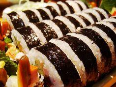 김밥(gimbap) / Dried Seaweed Rolls(Korean Rolls)  Vegetables and cooked egg are placed on seasoned rice. The ingredients are then rolled in dried seaweed and sliced into bite-sized pieces.