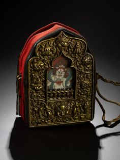 Gau (amulet box) of brass, shrine-shaped box containing painting of Buddhist deity, lid decorated with the Eight Auspicious Symbols, red woollen textile wrapping, and strap with leather ties, worn by a man for spiritual protection: Tibet, 19th century AD Gau