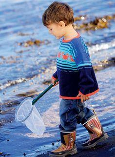 Krabbeblusen er lige sagen til en ferie ved stranden. Den luner uden at være for varm. Blusen er strikket på rundpind til ærmegabene. Den kan bruges af både drenge og piger.