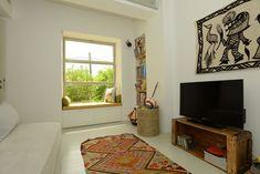 ובחזרה לקומת הקרקע: חדר המשפחה גם הוא מלא אור ומעוצב מחומרים פשוטים, עם ספסל ישיבה מתחת לחלון גדול ( צילום: רמי חכם )