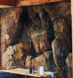 Sculpted shotcrete/concrete for indoor swimming pool with slide. Painted to look like granite. Planters and waterfalls are in the rock fractures & crevasses.