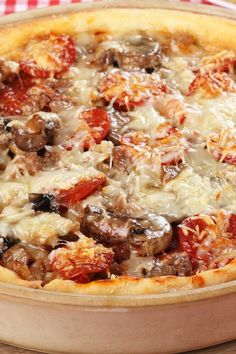 Chicago Style Deep Dish Pizza Recipe - frozen bread dough topped with Italian sausage, mozzarella cheese, mushrooms, onion, tomatoes, oregano, fennel seed, garlic, pepperoni, and parmesan cheese.