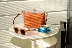 Lifestyle advertising photography of handbag and sunglasses with coffee in afternoon sunshine #advertisingphotography #productphotography #sunglasses #handbag #coffee #sunshine
