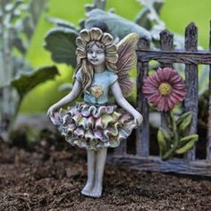 """Fairy Eden stands tall in her rainbow colored dress and sunflower petal headdress. The size of this Fairy Garden item is3.5"""" Tall and it is made ofResin. Well HelloMy Fairy Gardens Friend!"""