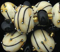 Onyx Firefly torchwork beads  |  Artist: Debbie Sanders Glass (DSG Beads)  |  debbiesandersglass.com  |  via etsy
