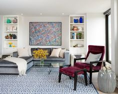 Modern living room with graphic blue Greek key rug, silver blue velvet sectional sofa, glass coffee table and burgundy accent chair and otto...
