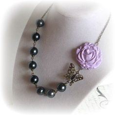 Handmade Asymmetrical necklace. Chic hand sculpted lavender rose pendant, filigree butterfly, dark grey pearls, & chain make up the design of this piece