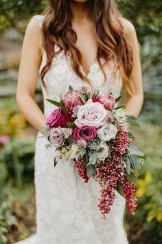 Cascading Wedding Bouquet: Berry Colored Roses, Lavender Roses, Red-Violet Queen Protea, Purple Alstromeria, Blushing Bride Protea, Pepper Berries, Green Seeded Eucalyptus