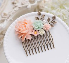 Blush Pink Mint Green Wedding Bridal Hair Comb. This is a romantic floral hair comb. It features a filigree brass comb embellished with beautifully sculptured resin flowers in blush pink, mint green and ivory. Antiqued gold brass leaf branches and a cream white pearl cabochon add beautiful details to the comb.  Comb: approx. 3.2 long (82mm) x 3.1 tall (80mm) including leaf branches.  Large moss green flower: approx. 35mm x 45mm  ♥ More hair comb designs are available here: www.etsy.com/...