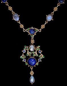 Liberty & Co. - JESSIE M. KING (1875-1949) LIBERTY & Co. An delicate Arts & Crafts gold necklace. The pendant set with cabochon sapphires and mother-of -pearl within a border of green enamelled leaves and small sapphires  with a moonstone drop. The enamelled chain set sapphires and moonstones. British. Circa 1900.