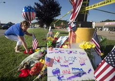 Cathy Sosbee places a balloon and flowers at a makeshift memorial outside a military recruiting center on Friday, July 17, 2015, in Chattanooga. Mohammad Youssef Abdulazeez attacked two military facilities on Thursday, in a shooting rampage that killed four Marines.  Photo by Associated Press /Times Free Press.