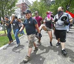 """One man wearing a black hat with the slogan """"Make America Great Again,"""" identified as a white supremacist, is kicked by a female counter protester wearing a pink bandana at a rally, Saturday, July 8, 2017, at the New Haven Green."""
