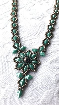Turquoise green diamond bead pewter seed bead beaded statement necklace. Central motif sewn with a genuine Swarovski crystal pearl in Brown together with galvanised metallic pewter (grey) seed beads, matte turquoise green seed beads and Turquoise green blue diamond shape