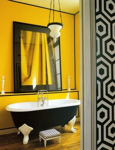 Look at those Legs!    Black vintage bathtub. Black and white print wallpaper and stool. Exaggerated mirror.