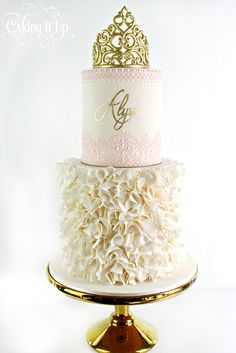 Soft, royal elegance. Two tier Birthday cake featuring pretty ivory ruffles and top tier is embellished with delicate edible lace, hand piping and hand painted name. Handmade royal fondant cake topper crown. www.facebook.com/cakingitup