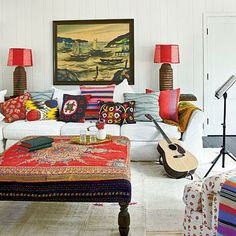 Design Kathryn Ireland ties most of her fabrics together with a shared color: red, which is seen on several fabrics, the ottoman, lamp shades, and even in the painting. Coastalliving.com
