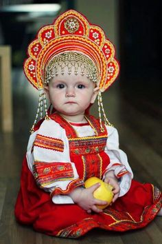 this baby is wearing traditional Russian clothing, meant for women to emphasize their inner dignity and emotional restraint.