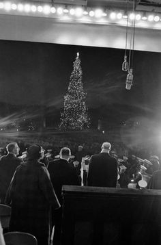 President Eisenhower, right, faces the National Christmas Tree as he lighted it in Washington formally opening the annual Christmas Pageant of Peace on Dec. 23, 1960. The tree is erected in the Ellipse, a park just south of the White House.