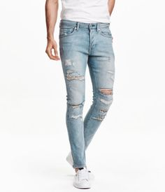 Light denim blue. 5-pocket, low-rise jeans in washed stretch denim with heavily distressed details, button fly, and skinny legs.