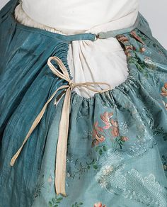 Robe à la Française, detail - 1760-70, French - the MET [Nice view showing the plain fabric of the top/back of the petticoat, hidden under the gown, as well as the drawstrings for arranging over side hoops and the hook and ring that closes the waistband.]