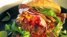 Hamburger av elgkjøttdeig eller annet vilt servert med kryddersyltet sopp, tyttebærrømme, bacon, rødløk og salat.
