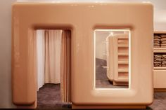 Underwear, shapewear and loungewear items are displayed inside chunky, beige cupboards fitted with hooks. Built-in shelves and nooks offer additional display space for clothes