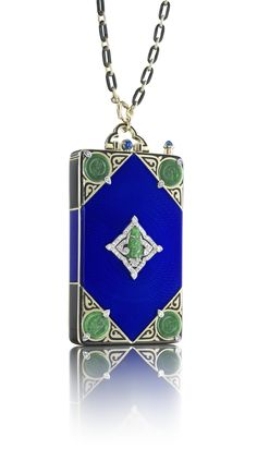 Rectangular sliding vanity case centering upon blue guilloché enamel, the four corners accented by circular carved jadeite discs with diamond accents over a gold and black enamel background, the center placque depicting a carved jadeite buddha within an ornate lozenge frame of diamonds, with a cabochon sapphire thumbpiece, suspended from a black enamel and gold chain; interior section slides out of the case from the top revealing a writing tablet, mirror, compartment, detachable lipstick…