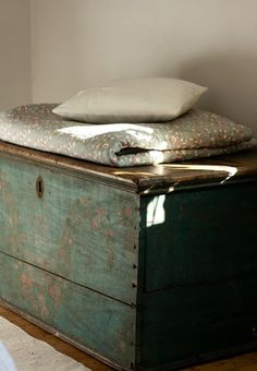 always have a trunk like this in a spare room with different types of pillows (firm, fluffy) and blankets