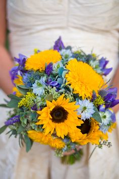Lots of small simple touches of color to accentuate the sunflowers.The bridal bouquet was created with teddy bear sunflowers, regular sunflowers, solidago, blue nigella, blue delphinium, blue veronica, seeded euc, and antique blue green hydrangea. This bouquet was a real beauty!!!