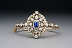 """Made by the Jewellers to the British Crown, Hunt & Roskell, in the last decades of Queen Victoria's reign. Openwork center set with an oval-cut royal blue Burmese sapphire, within a larger cluster of diamonds.  Oval diamond section measure 1 1.2"""" long, 1 1/4"""" across.   Convertible into a brooch.  $23,000."""