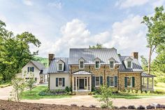 """Exterior - 2015 Charlottesville Idea House Tour - Southernliving. """"This is an updated take on typical rural Southern farmhouses,"""" explains Rosney Co. """"Rather than whiteclapboard, we used taupe- and orange-toned stone quarried in West Virginia. This helps connect the houseto its location in the foothills of the Blue Ridge Mountains.""""    This 1 1/2-story house is flanked by two chimneys."""