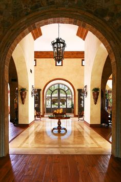 Through the stoned front pavilion you are greeted by massive hand forged wrought iron doors that open to a light filled and elegant entry with soaring ceilings