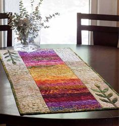 This quilted table runner, complete with appliqué flowers, will feel at home in any style decor.