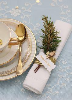 Tavola dai dettagli oro e segnaposto con rametti d'abete per rendere preziosa la…