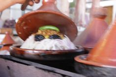Tangine being cooked. The name of the dish comes from the pot that is used in the cooking process. It is mainly a meat dish topped with vegetables and couscous. Some yummy food for Lisa in Morocco.