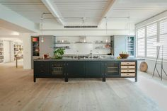 Soho Factory loft style kitchen featuring the Osea Island with Belgian Fossil Stone worktops and forged blacksmith blackened Steel handles.