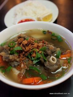 Ox-tail soup, with potato and carrot chunks, topped with green onions and fried shallots