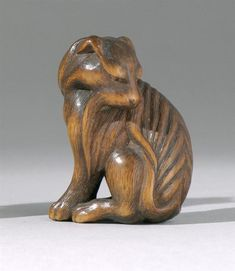 "WOOD NETSUKE Late 19th/Early 20th Century Depicting a dog with finely carved fur details. Inlaid eyes. Faintly signed on plaque on base. Height 1.5"" (3.81 cm)."