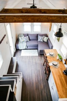 The Modern Farmhouse from Liberation Tiny Homes. A charming 24' long tiny house with a kitchen, living room, bathroom, and loft.