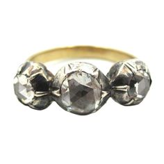 c 1830. Unusual handcrafted original Georgian era 3-stone ring composed of 18 karat yellow gold and topped with silver, featuring 3 collet-set Rose Cut diamonds weighing an estimated 0.90 Carats in total. Traditional Georgian era closed foil backed setting.