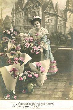 美しい街並みを背景ににこやかに花を売る女性のポストカード。モノクロの写真にほのかな色付けが施された幻想的な雰囲気です。マリーより夫妻へ新年のあいさつを兼ねたノエルのカードです。フランスの蚤の市でセレク…