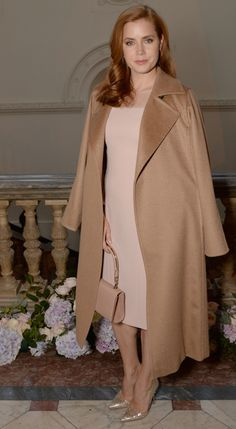 Ms. Adams, wearing the iconic Manuela wrap coat, dusty pink sheath dress with see-through neckline and carrying a nude handbag, all by Max Mara, looked exactly like every woman dreams of looking on...