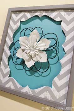 This chevron-patterned wall plaque features a beautiful layered metal flower in it center.