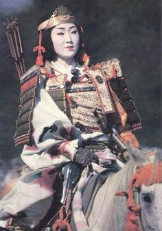 Onna-Bugeisha were female warriors in feudal Japan -- popular weaponry included a  naginata (a rod with a curved blade at the tip) or bow.