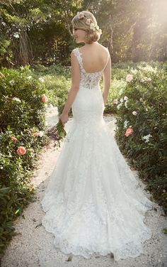 This gorgeous Essense of Australia lace over satin fit-and-flare wedding dress is no exception. It is the perfect union of class and elegance with its fitted bodice, lace back detailing, flared skirt, and traditional chapel train. The back zips up under crystal buttons. You'll love how this silhouette accentuates your feminine curves.