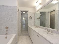 Master bathroom with Carara marble counter top and walls, deep step in tub and…